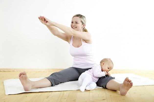 Молодая мам с малышом занимается фитнесом