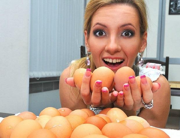 Женщина держит куриные яйца