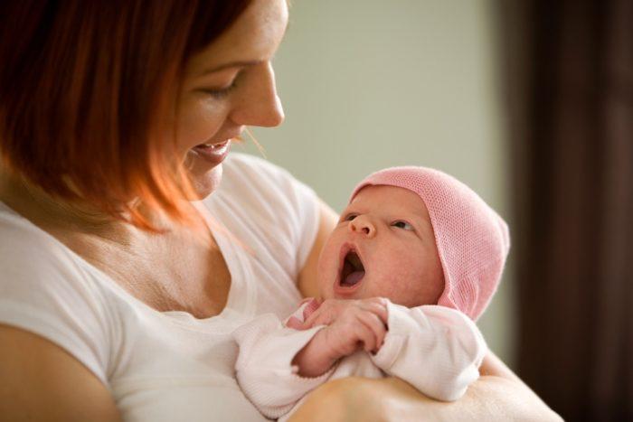 новорожденный малыш у мамы под грудью